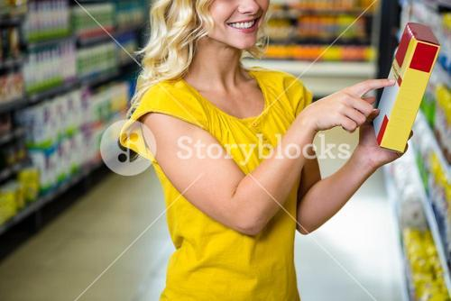 Smiling pretty blonde woman pointing a box