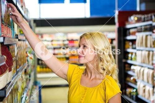 Smiling blond woman picking product on shelf