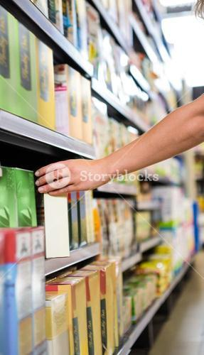 Cropped image of woman picking a box in shelf