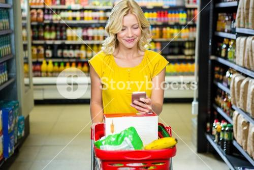 Smiling woman with smartphone pushing trolley in aisle
