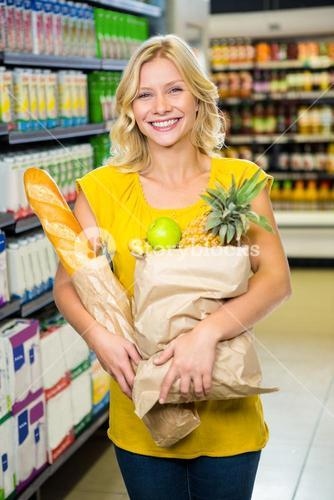 Smiling woman standing in aisle with grocery bag