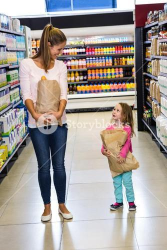 Mother and daughter holding paper bag