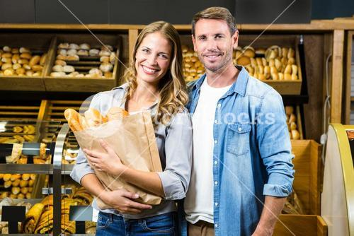 Happy couple holding paper bag