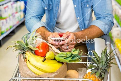 Man texting and grocery shopping