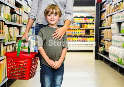 Cute boy doing grocery shopping with mother