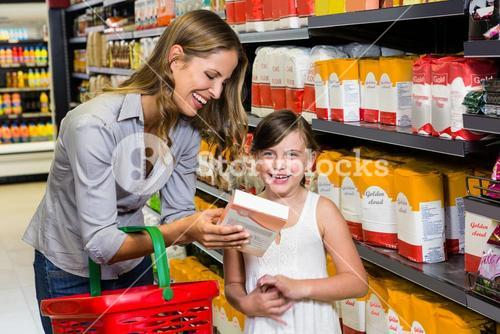 Mother and daughter reading ingredients on pack of flour
