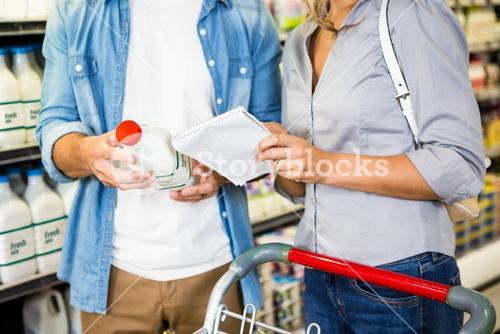 Couple reading the ingredients in a milk bottle