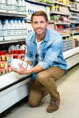 Handsome man reading the ingredients on a milk bottle