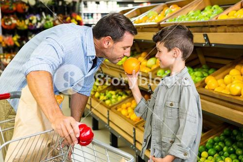 Father smelling sons orange