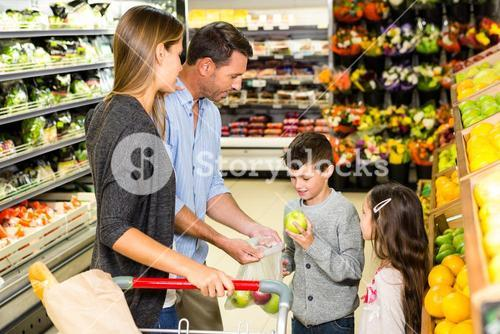 Cute family choosing groceries together