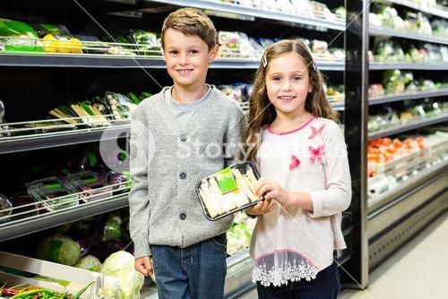 Cute siblings doing grocery shopping