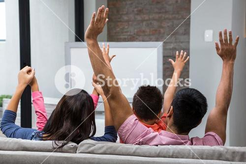 Happy family rejoicing while watching tv on the sofa