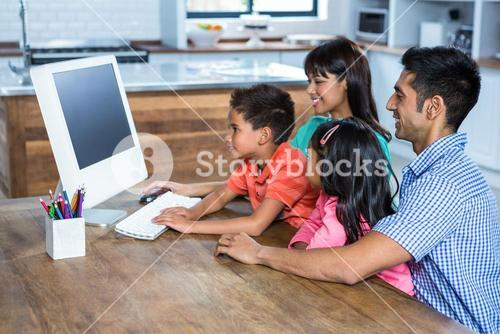 Happy family using computer in kitchen