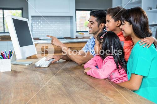 Happy family using computer in the kitchen
