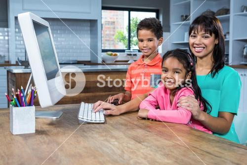 Happy mother using computer with her children