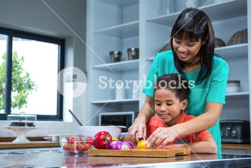 Smiling mother cooking with her son