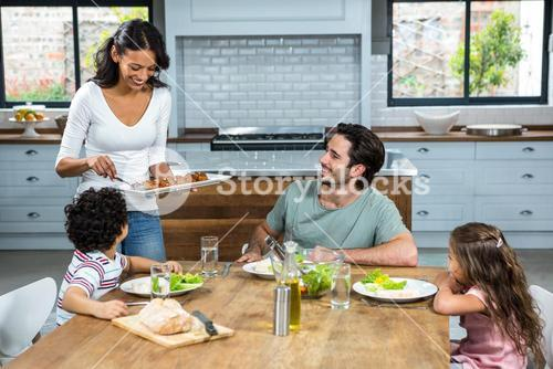 Smiling mother giving food to her children and husband