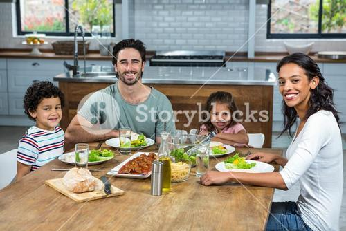 Happy family eating together in the kitchen