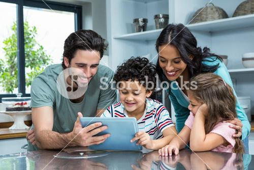 Happy family using tablet in kitchen