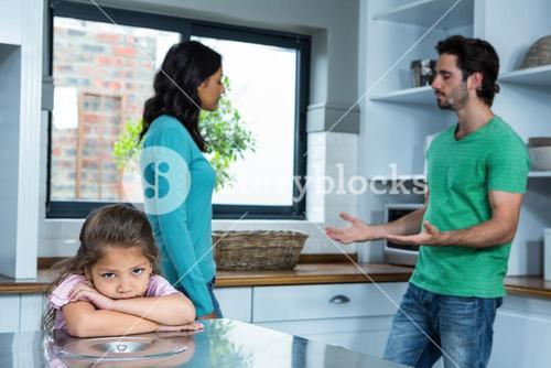 Sad child listening to parents argument