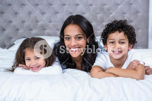 Smiling mother with children on the bed