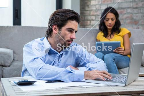 Serious man paying bills in living room