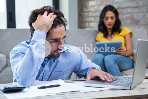 Worried man paying bills in living room