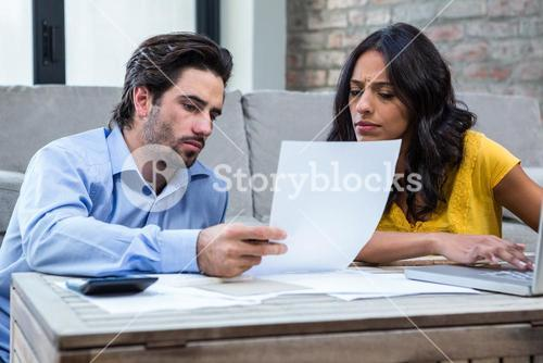 Couple in living room paying bills