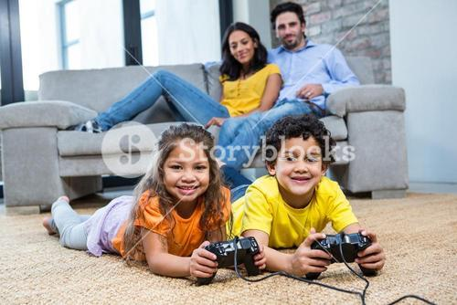 Children playing video games on the carpet in living room