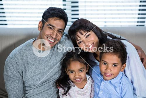 Happy young family posing together on the couch