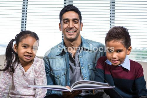 Happy father reading a book for his children
