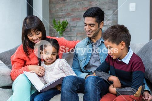 Happy young family reading a book together