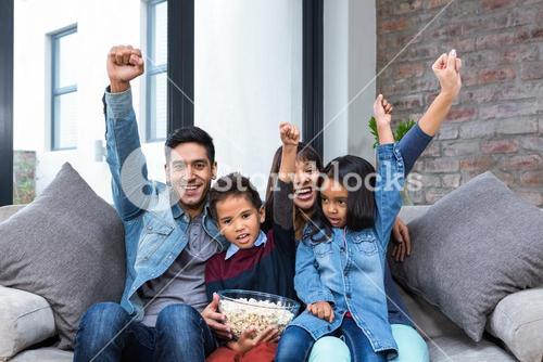 Happy young family eating popcorn while watching tv
