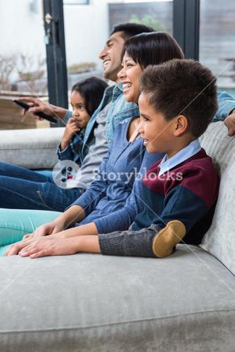 Happy young family watching tv
