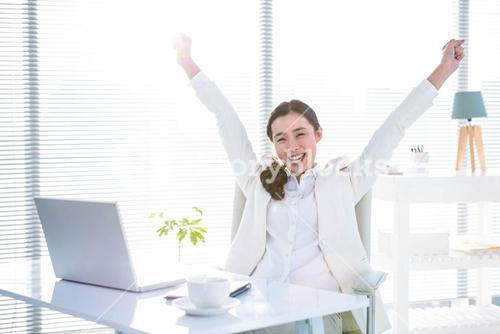 Businesswoman rejoicing with arms outstretched
