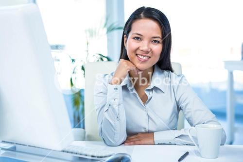 Smiling businesswoman with chin on fist