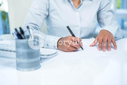 Businesswoman writing on white paper