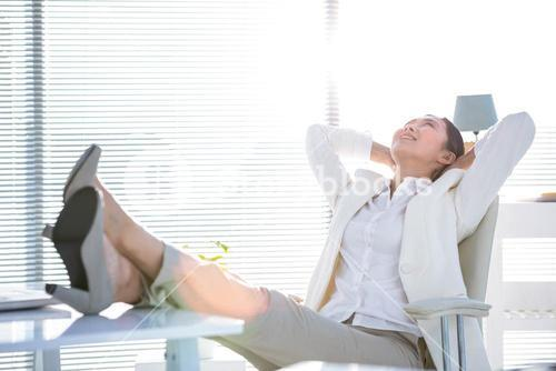 Businesswoman relaxing with legs on desk