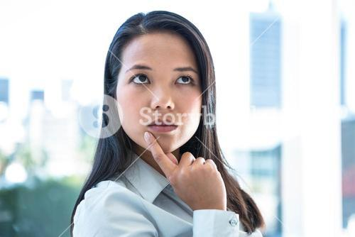 Thoughtful businesswoman with finger on chin