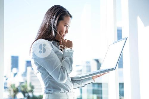 Businesswoman with finger on cheek using laptop
