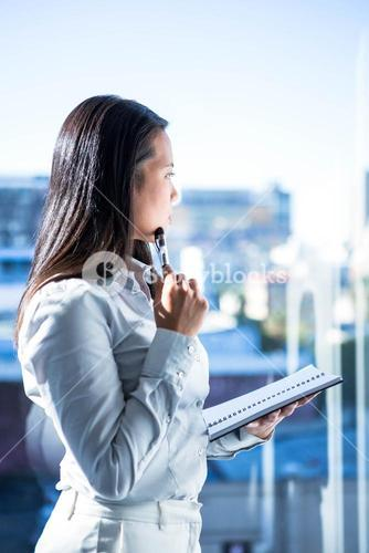 Thoughtful woman with pen on cheek holding notepad