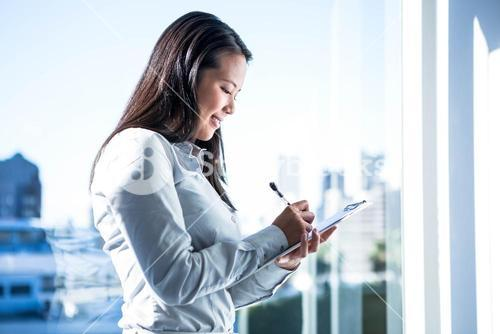 Smiling businesswoman writing on notebook