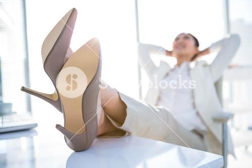 Relaxed businesswoman sitting with her feet up