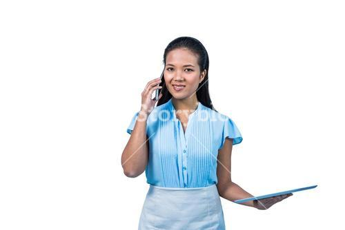 Smiling businesswoman with tablet phoning