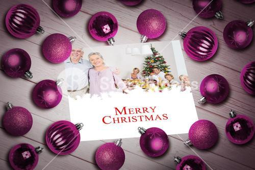 Composite image of christmas baubles on table
