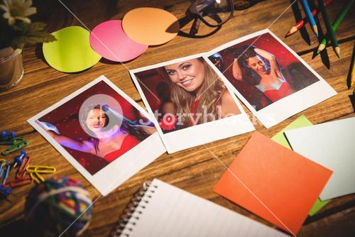 Composite image of high angle view of office supplies with blank instant photos