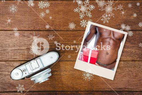 Composite image of mid section of shirtless macho man holding gifts