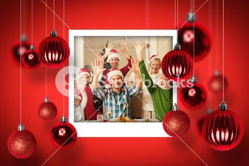 Composite image of happy extended family in santa hat cheering at camera