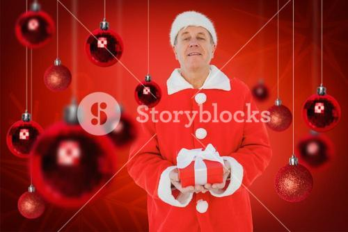 Composite image of festive man holding gift