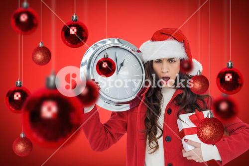 Composite image of surprised brunette holding a clock and gift